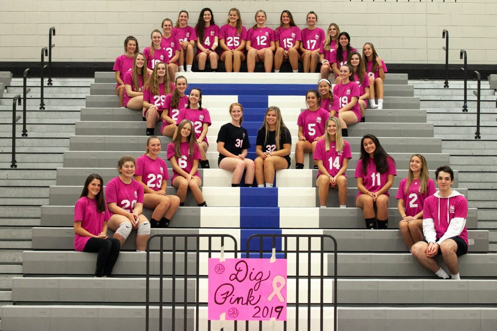 Team members sit on the school bleachers in a breast cancer ribbon formation.