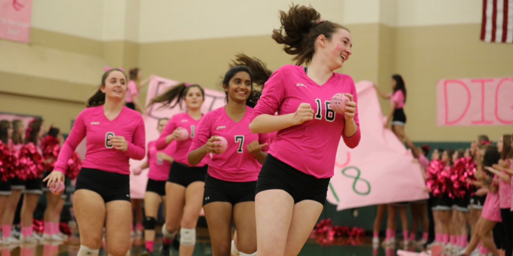 Lisa Alexander and her teammates running on the volleyball court.